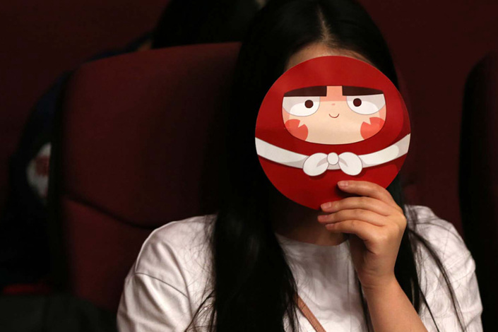 "A viewer covers her face with a fan featuring a character from the adult-oriented domestic cartoon ""Dahufa"" in June 2017 at a theater in Shenyang, Liaoning province. Photo: IC"