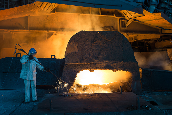 A worker stands next to a vat of molten iron in July 2016 at a Wuhan Iron and Steel Group plant in Central China's Hubei province. Photo: IC