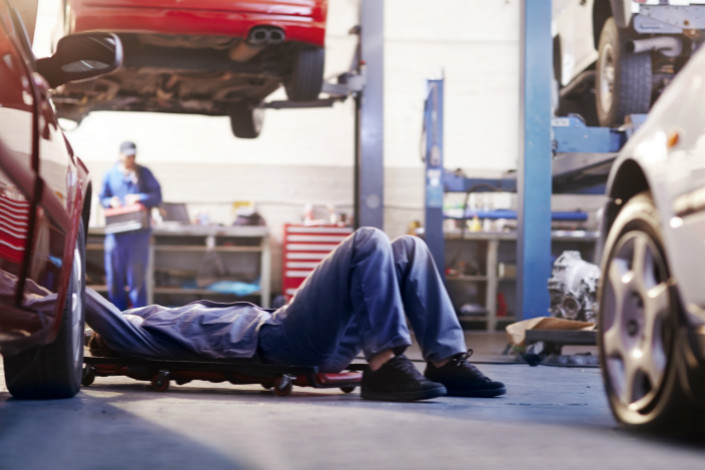 Mechanic under car in auto repair shop. Photo: VCG