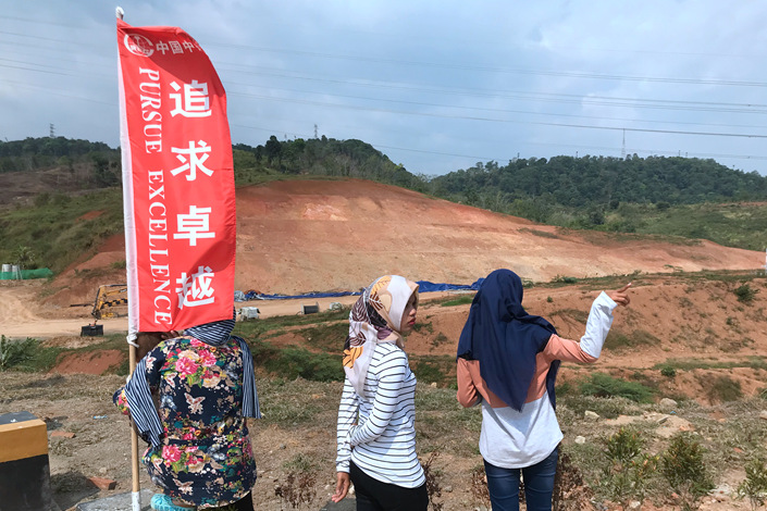 Indonesian women look at the  construction site of the country's high-speed rail Walini tunnel on Sept. 11. Photo: Takehiro Masutomo/Caixin