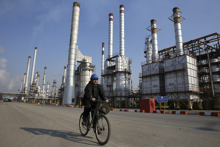 An Iranian oil worker rides his bicycle through Tehran's oil refinery south of the Iranian capital in December 2014. Photo: IC