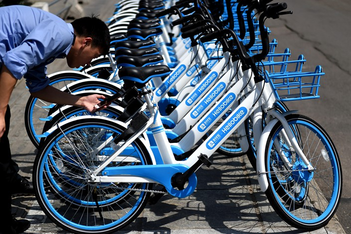 A man uses his mobile phone to unlock a Hellobike bicycle on the streets of Luoyang, Henan province on Sept. 11, 2017. Photo: IC