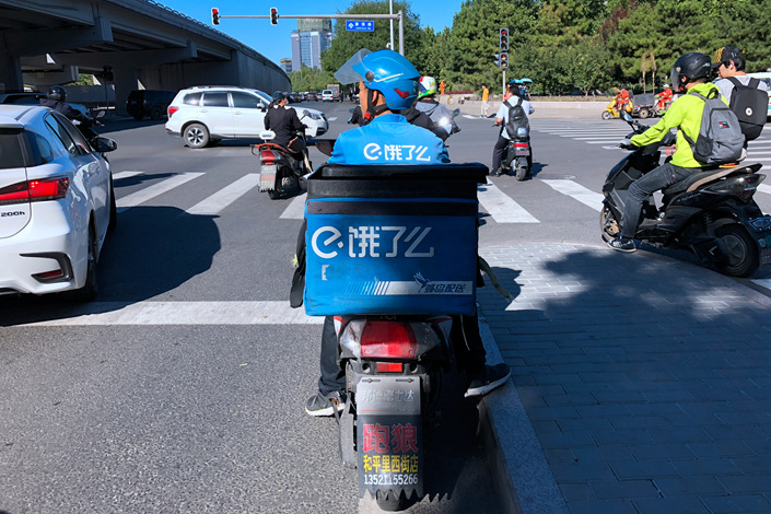 An Ele.me delivery driver stops at a traffic light in Beijing on Sept. 7. Photo: Wu Gang/Caixin