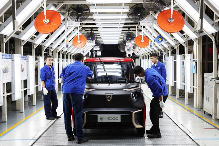 Workers at SAIC-GM-Wuling Automobile conduct a final inspection of a new energy vehicle at the joint venture's Qingdao factory on Sept. 28. Photo: VCG