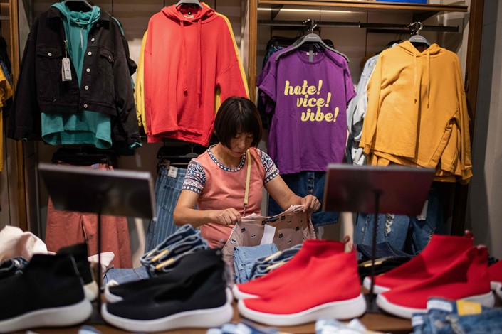 A shopper examines a T-shirt at a mall in Beijing on Sept. 10. Photo: VCG