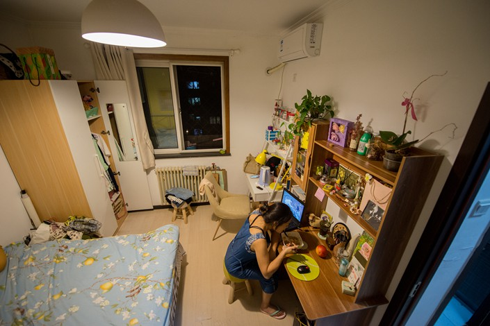 A woman eats dinner in a rented Ziroom apartment in Beijing on Sept. 4. Photo: VCG