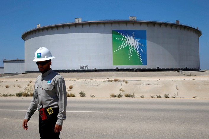 An employee of the Saudi Arabian Oil Co. walks near an oil tank at the company's Ras Tanura oil refinery and oil terminal in Saudi Arabia on May 21. Photo: VCG