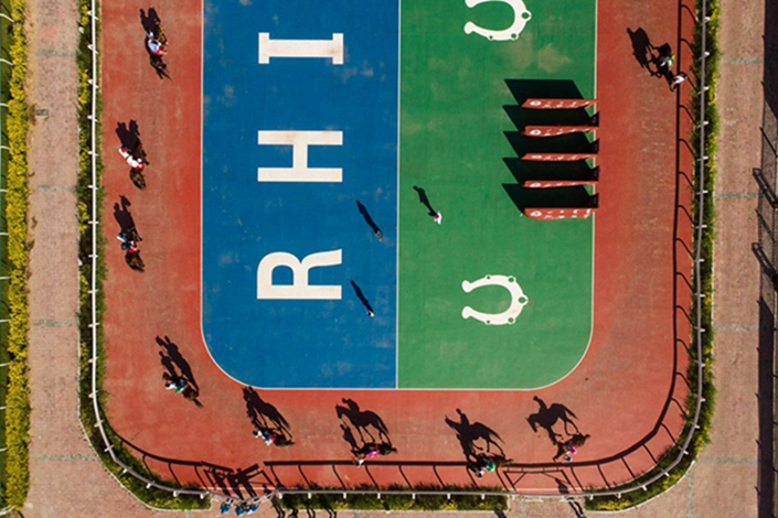 Racehorses are introduced before a race at the Horqin Right Middle Banner racecourse in the Inner Mongolia autonomous region on July 27. This is one of the government-sponsored events as part of the Nadam Fair, which draws hundreds of thousands of local spectators. Guo Xianzhong/Caixin