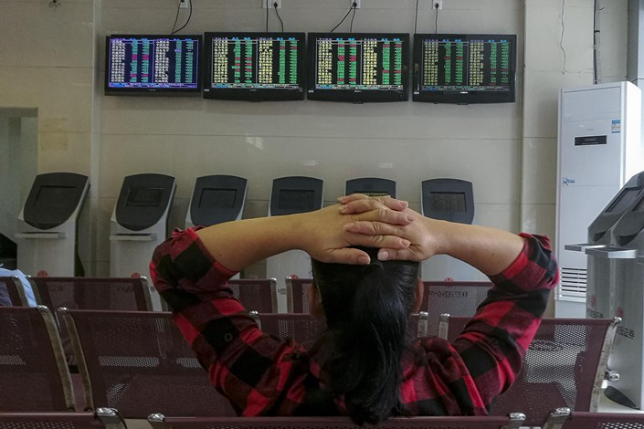 A woman sits in the client area of a securities trading company in Haikou, Hainan province on Oct. 18. Photo: VCG