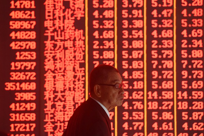 An investor watches the boards Monday at a stock exchange in the eastern city of Hangzhou. Photo: VCG