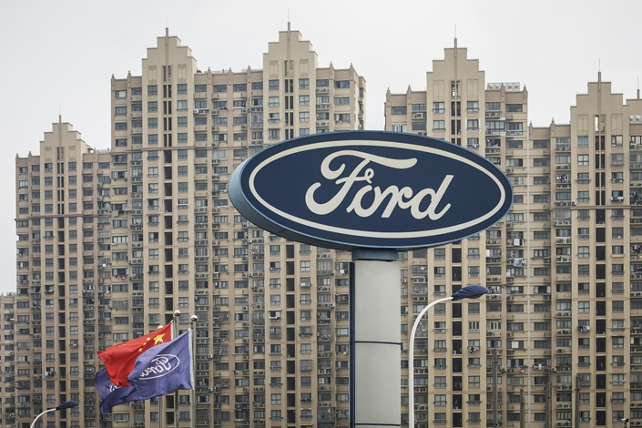 A Ford Motor Co. sign is seen next to a Chinese national flag and Ford cooperate flag in Shanghai on July 8. Photo: VCG