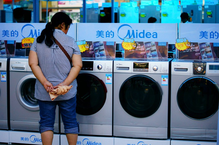 A customer looks over Midea Group Co. Ltd. washing machines at a home-appliance fair in Yichang, Hubei province, in September 2017. Photo: IC