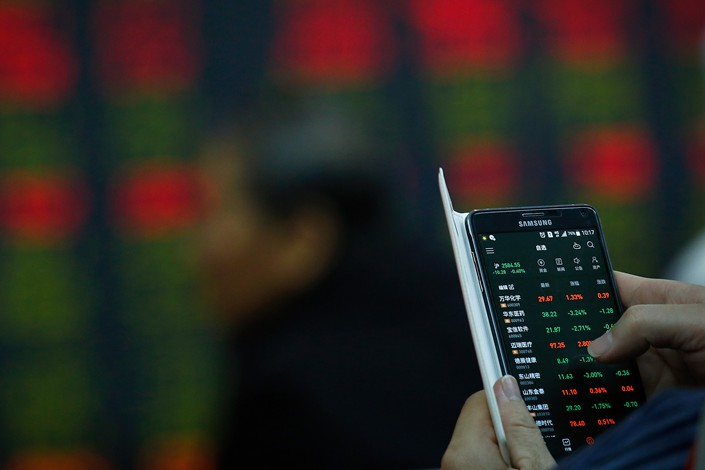 An investor checks stock prices on his smartphone at a brokerage in Beijing on Wednesday. Photo: IC