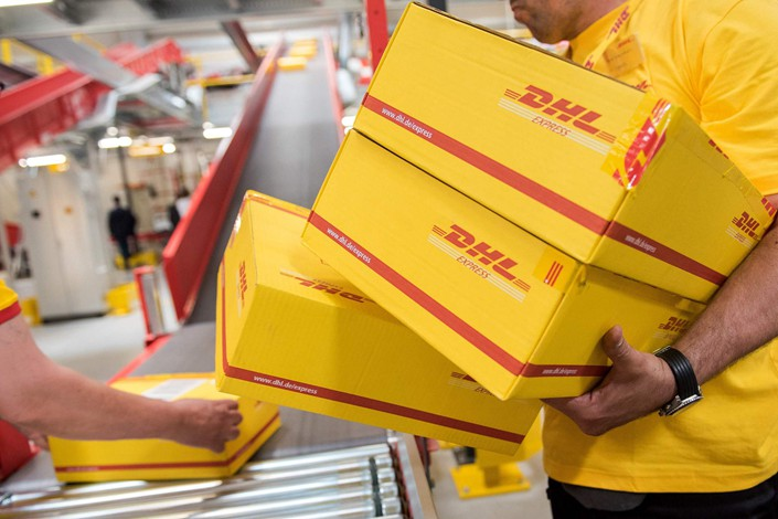 Workers carry packages at a DHL Group logistics center in Hamburg, Germany in May 2017. Photo: VCG