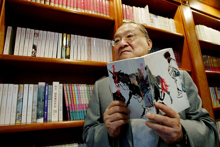 Novelist Louis Cha, who wrote under the name Jin Yong, holds his book