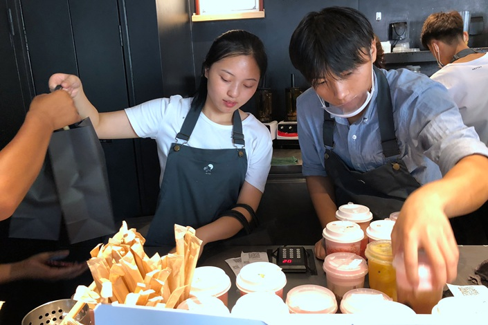 Employees of a drink outlet in Beijing's Sanlitun area serve beverages on Aug. 16. Photo: Wu Gang/Caixin