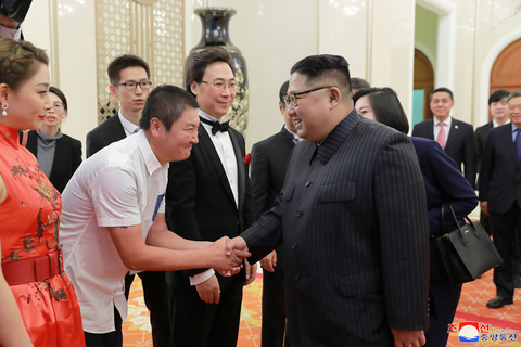 Kim shakes an artist's hand during the performance. Photo: VCG
