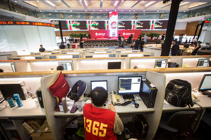 A trader sits in front of a computer at his work station at the Shanghai Stock Exchange.Photo: VCG