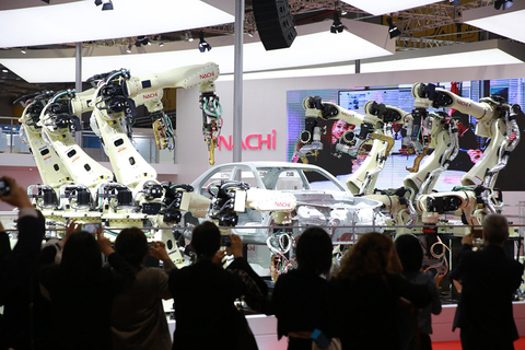 A Nachi Robotic System robot spot-welds a car body on Monday in front of expo attendees. Photo: VCG