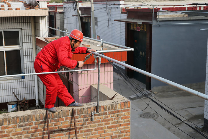 A worker installs gas pipes in a village in Cangzhou, Hebei province in November 2016. Photo: VCG