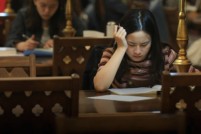 A student pores over documents in a university library in the western city of Chongqing on Oct. 11. Photo: VCG
