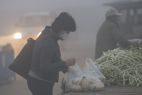 A Beijing resident shops at a vegetable market in heavy smog on Wednesday. Photo: VCG