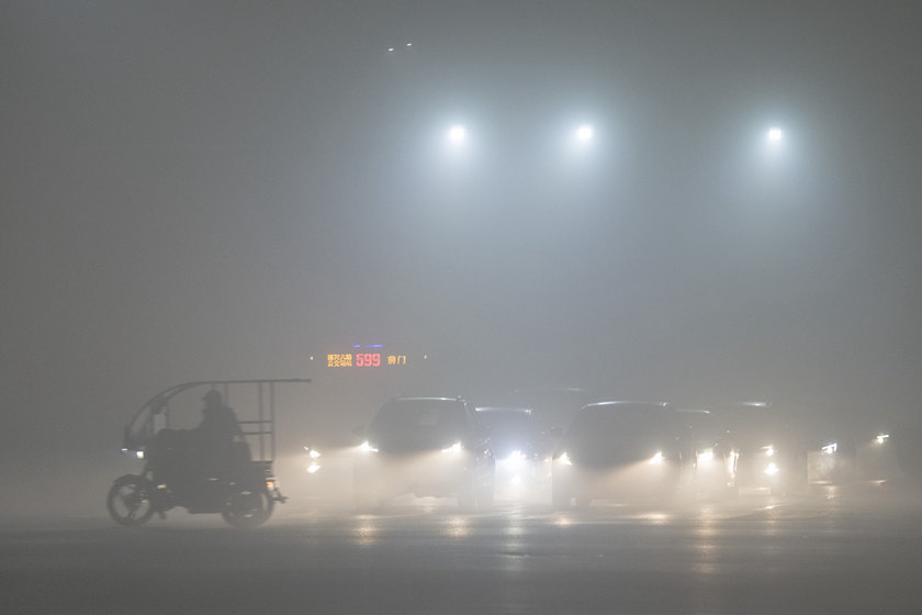 Beijing motorists drive through heavy smog in the city on Wednesday. Photo: VCG