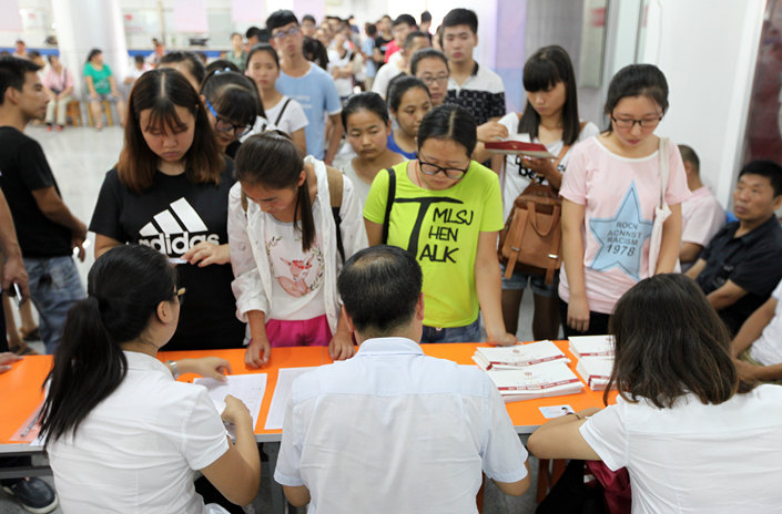 Eligible college freshmen in Baoji, Shaanxi province, line up to receive university financial aid in August 2016. Photo: VCG