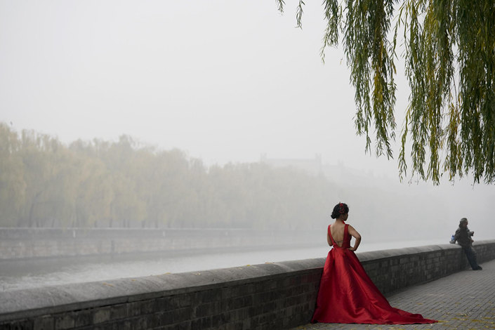 Couples take wedding photos near the Palace Museum on Wednesday as heavy smog envelopes Beijing. Photo: VCG