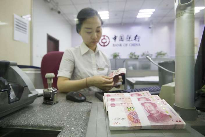 A worker counts cash at a Bank of China branch. Photo: VCG