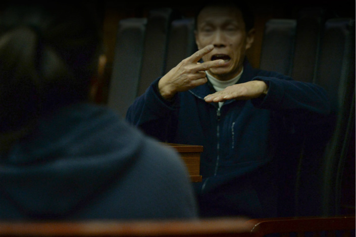 A man with a hearing impairment communicates with his court interpreter in Beijing in November 2015. Photo: IC