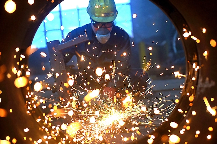 A worker polishes industrial parts at a private foundry in Shandong Province. Photo: VCG