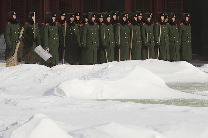 Paramilitary police officers carry snow clearing equipment in Beijing. Photo: Bloomberg