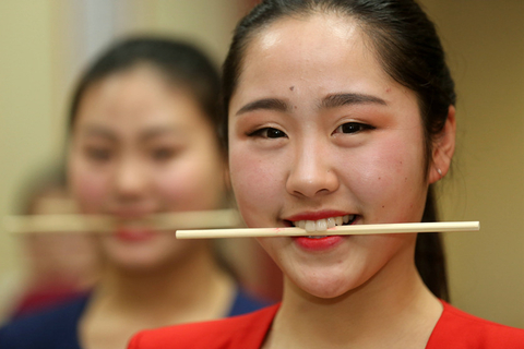 Women who want to major in performing arts practice smiling while holding chopsticks with their teeth during a training class in Bengbu, Anhui province, in December 2015. Photo: IC