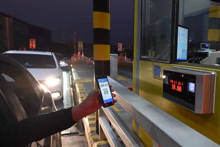 A motorist uses a cellphone to pay a toll at the Shugang toll station on the Suyang Expressway in Yangzhou, Jiangsu province, on Oct. 23. Photo: VCG
