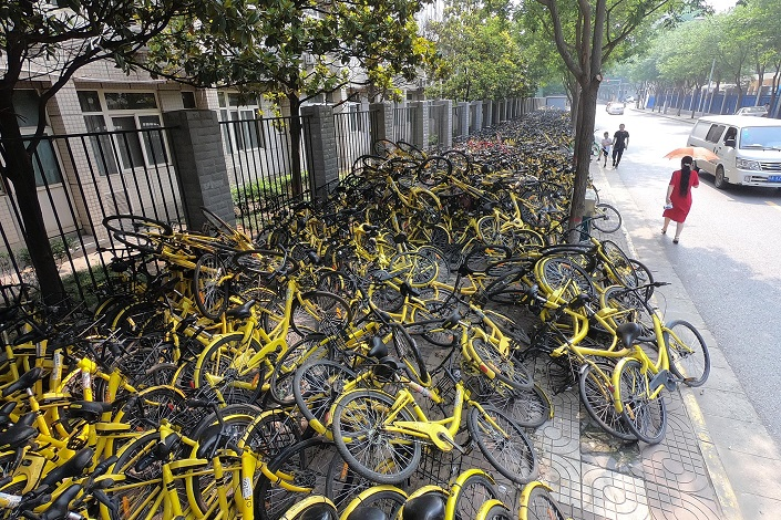 Mobike's signature yellow bikes block the sidewalk on a street in Xi'an. Photo: VCG