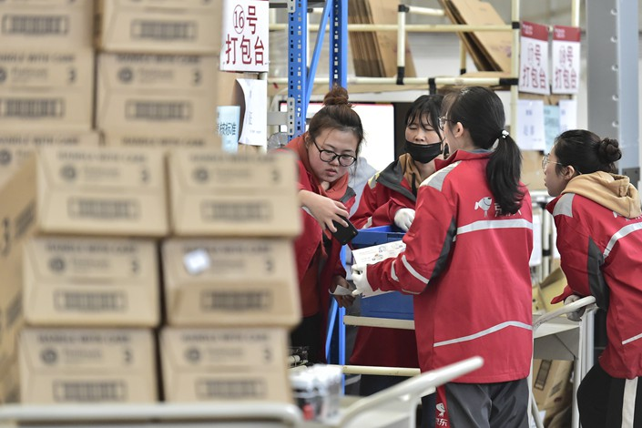 JD.com Inc. workers sort imported goods at a warehouse in Tianjin on Nov. 11. Photo: IC