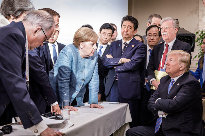German Chancellor Angela Merkel deliberates with US President Donald Trump on the sidelines of the official agenda on the second day of the G7 summit on June 9, 2018 in Charlevoix, Canada. Photo: Bloomberg/Getty