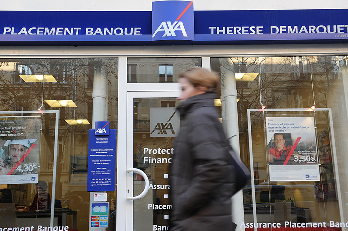 Pedestrians walk past Axa's headquarters in Paris, France. Photo: VCG