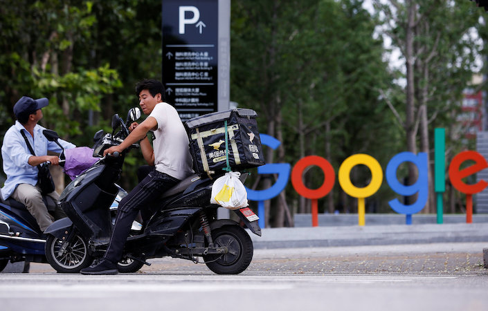 Food deliverymen wait outside Google's Beijing offices. Photo: VCG