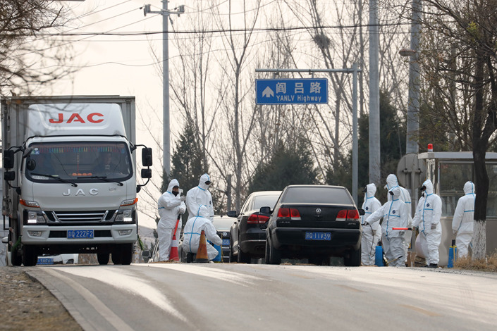 Workers disinfect passing vehicles on the outskirts of Beijing on Friday in an area affected by the African swine flu outbreak. Photo: IC