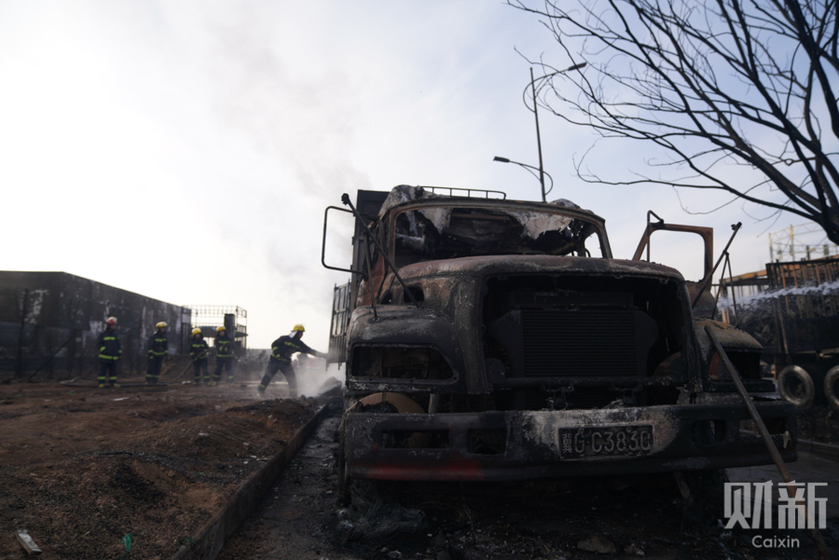 Smoke rises from a burnt-out truck at the site of an early Wednesday blast that killed 23 people and left 22 injured. Photo: Caixin_Gallery: Aftermath of Deadly Hebei Chemical Plant Explosion