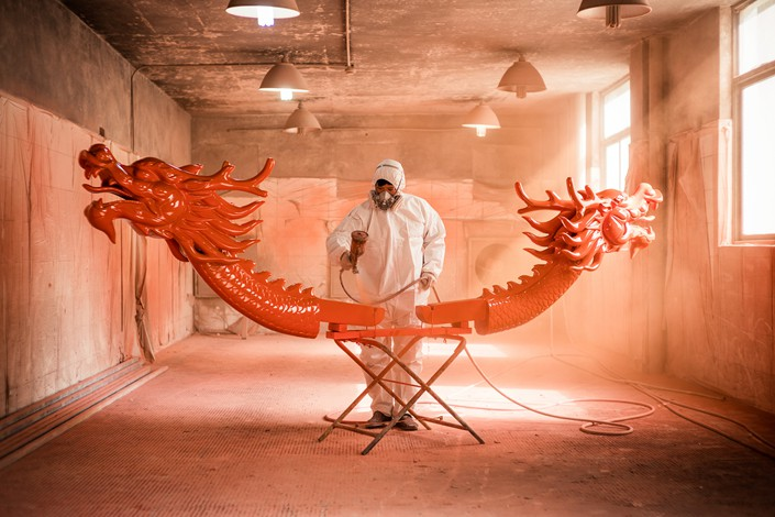 A worker spray-paints a dragon boat in East China's Zhejiang province on March 23. Photo: VCG