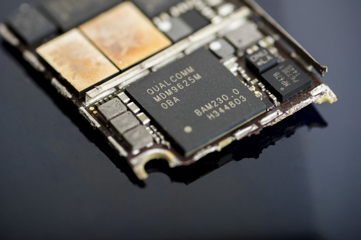 A Qualcomm chip inside an Apple iPhone 6 smartphone. Photo: Bloomberg