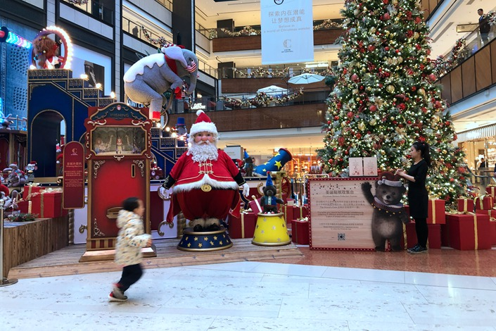 A child runs past holiday decorations Sunday in a department store in Beijing. Photo: Wu Gang/Caixin