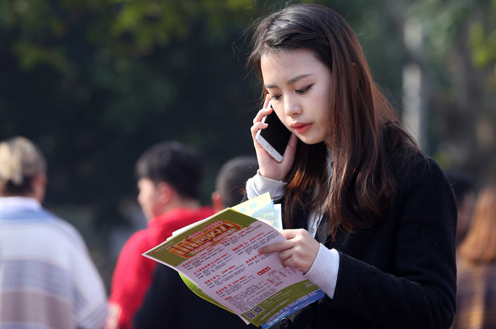 An attendee scours for jobs at a college graduation recruitment meeting held at Neijiang Normal University in Sichuan province on Nov. 25, 2018. Photo: VCG