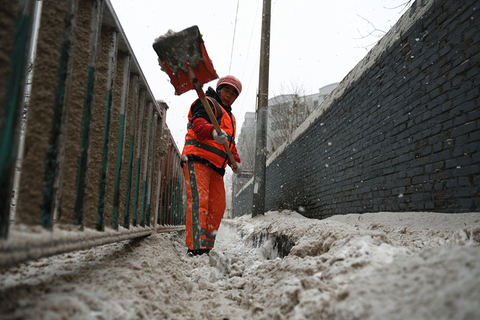 A sanitation worker cleans up the sandy snow. Photo: VCG