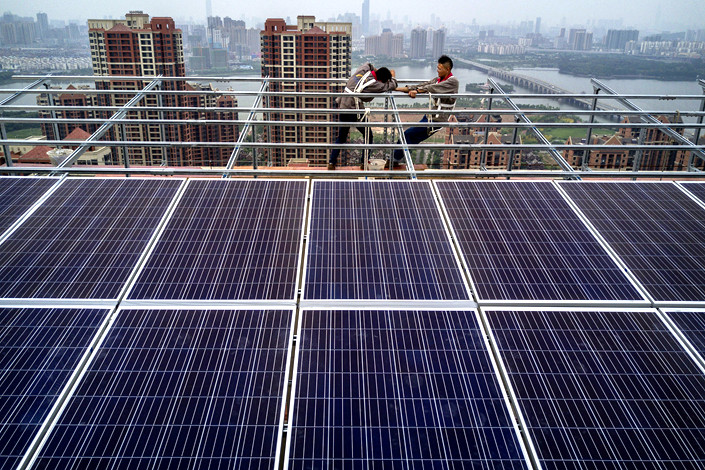 Wuhan Guangsheng Photovoltaic Co. employees in Wuhan, Hubei province, work on a solar panel project on the roof of a 47-story building in May 2017. Photo: VCG