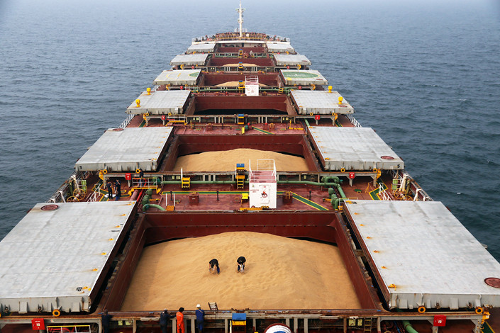 Workers take samples of soybeans on a ship at the port of Yantai in East China's Shandong Province in July 2016. Photo: VCG