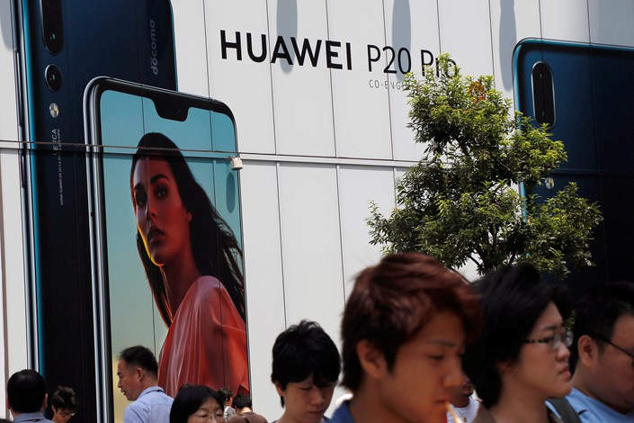 An advertisement for Huawei Technologies Co. Ltd. is seen outside an electronics store in Tokyo on Aug. 6. Photo: VCG